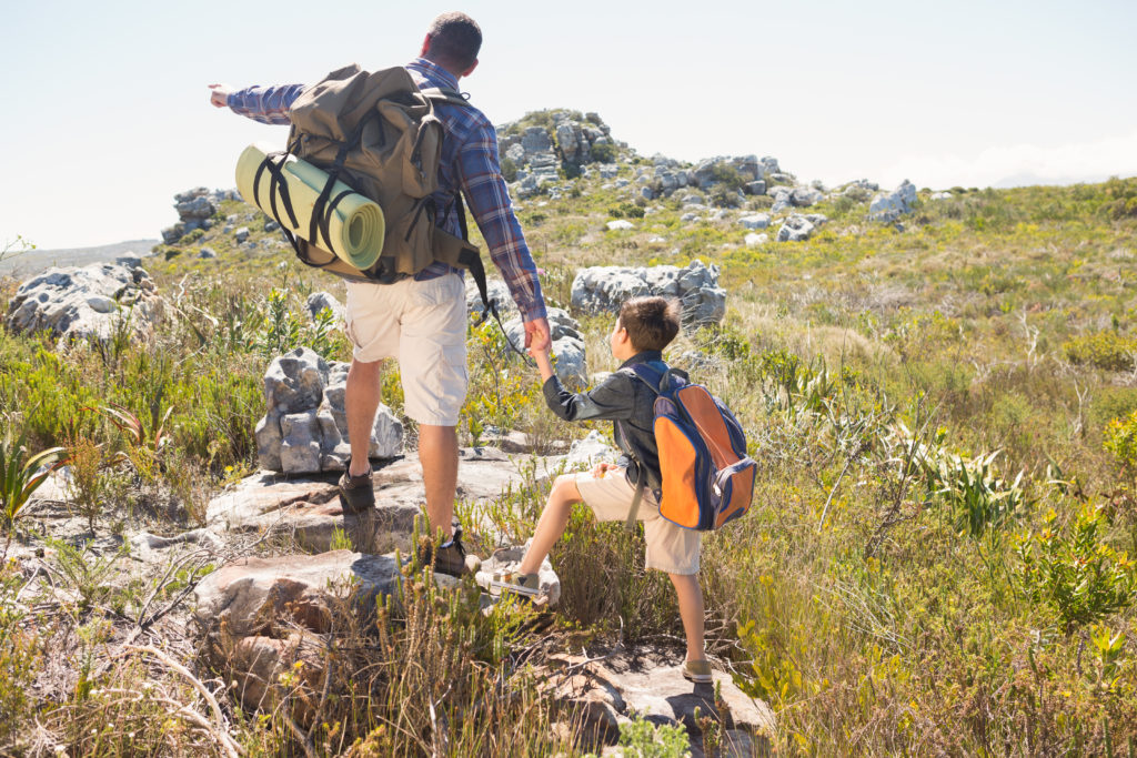 A adventurous parenting style man with his son hiking